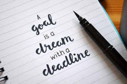 A GOAL IS A DREAM WITH A DEADLINE written in notebook on desk